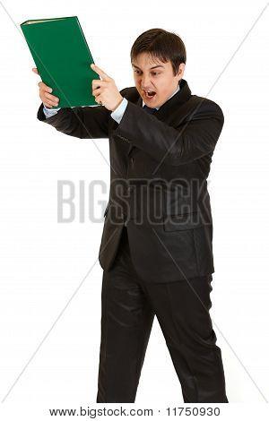 Stressed modern businessman brandishing folder with documents isolated on white