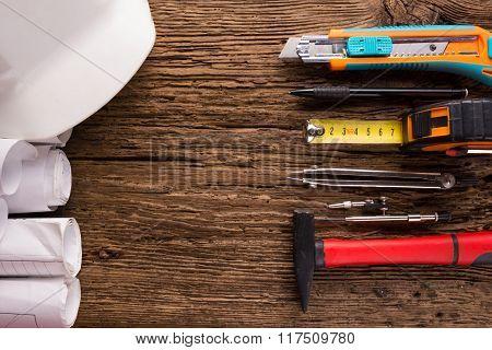 Architectural blueprint and white safety helmet, hammer, divider