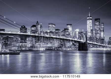 View of Manhattan with skyscrapers and old Brooklyn Bridge by night, New York City illumination