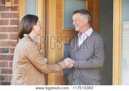 Woman Checking On Elderly Male Neighbor
