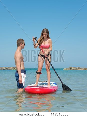 Boy And Girl On Stand Up Paddle