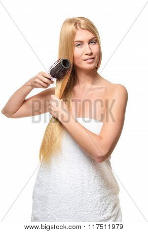 Young woman in a towel brushing her hair.