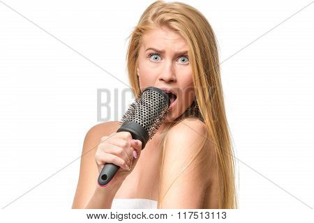 Pretty woman in towel singing using comb