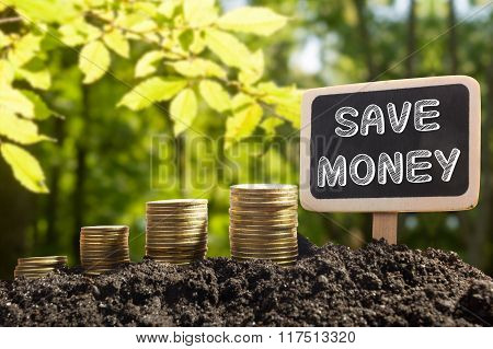 Save Money - Financial opportunity concept. Golden coins in soil Chalkboard on blurred urban backgro
