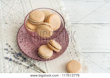 vanilla macaroons with lavender cream on white wooden background