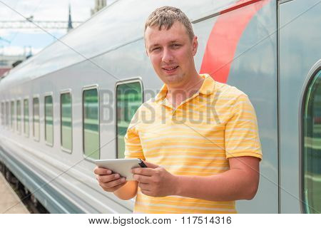 Happy Man Holding A Tablet Computer Near The Train