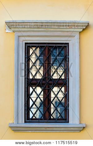 Yellow Wall Of A Building And Window With Black Grille