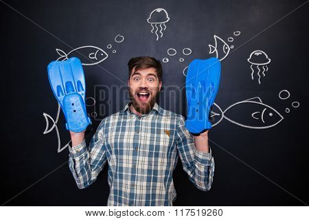 Excited amusing young man with blue flippers on hands standing over drawing of underwater world on blackboard background