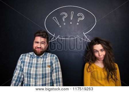 Ugly young couple joking and grimacing over chalkboard background