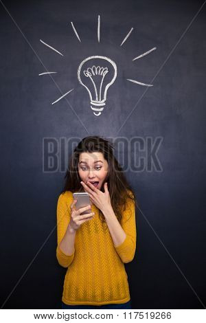 Amazed happy young woman with opened mouth using mobile phone over chalkboard background
