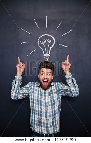 Amazed funny young man with tousled hair pointing up and having an idea standing over blackboard background