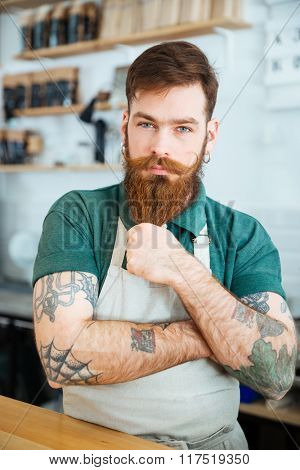 Attractive male barista with tattooed hands standing in coffee shop and touching his beard