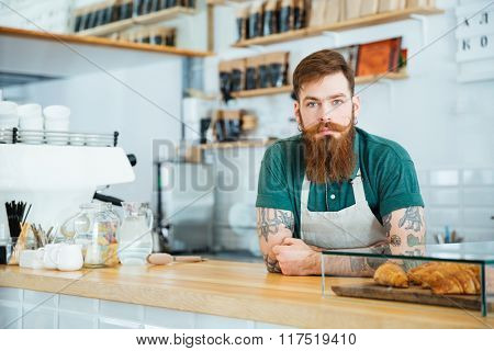 Portrait of bearded male barista standing in coffee shop and looking camera