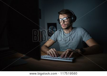 Concentrated young man in headphones sitting in dark room and using computer
