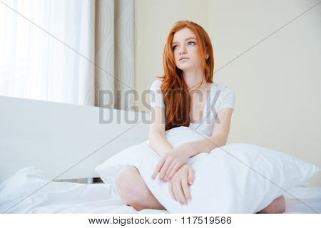 Thoughtful redhead woman sitting on the bed with pillow