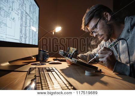 Focused young man in glasses repairing motherboard with soldering iron