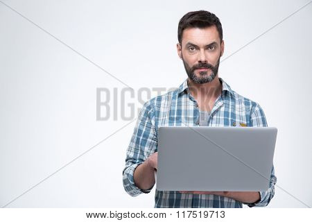 Serious man using laptop computer isolated on a white background and looking at camera