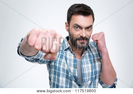 Handsome man punching with fist at camera isolated on a white background