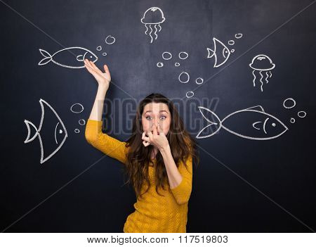 Funny cute young woman closed nose by hand and simulating deep diving under the sea over blackboard background