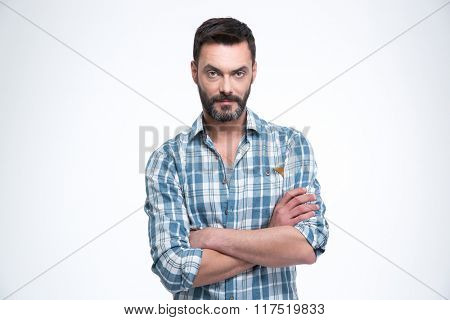 Serious man with arms folded standing isolated on a white background and looking at camera