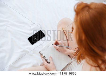 Top view of pretty redhead young woman writing in diary and listening to music from smartphone