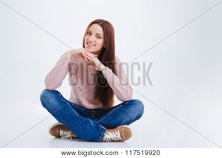 Happy woman in casual cloth sitting on the floor and looking at camera isolated on a white background