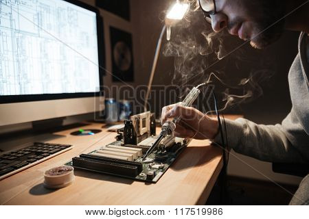 Closeup of serious young man using scheme on monitor and soldering iron for repairing motherboard