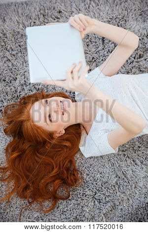Happy redhead woman lying on the carpet and using table computer