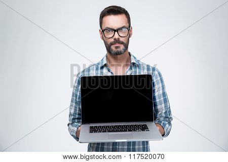 Handsome man showing blank laptop computer screen isolated on a white background