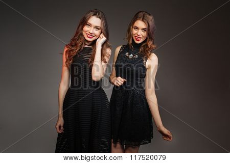 Two cheerful beautiful women in black dresses going to party together over grey background