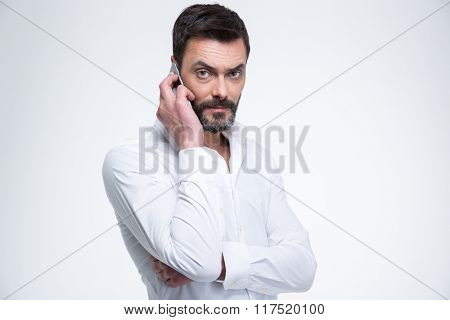 Mature businessman talking on the phone and looking at camera isolated on a white background