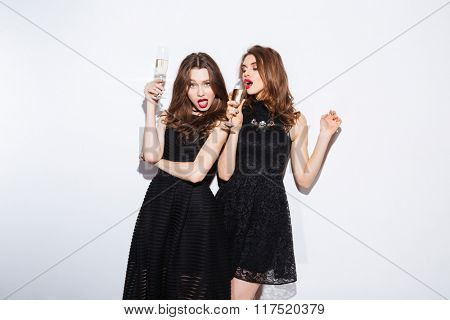 Two attractive women in night dress drinking champagne isolated on a white background