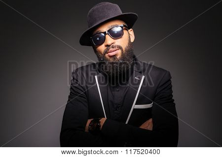 Serious afro american man in fashion cloth and glasses standing with arms folded over black background