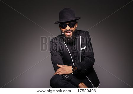 Cheerful afro american man in trendy cloth posing over black background