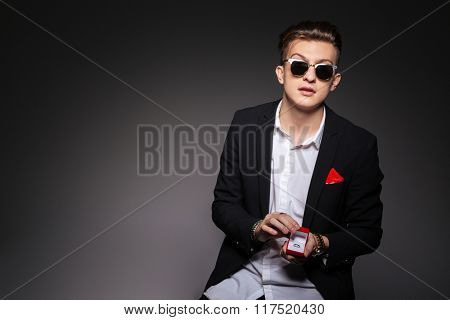 Fashion man holding box with a proposal ring over black background