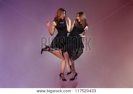 Full length portrait of a cheerful two women in night black dress dancing over purple background