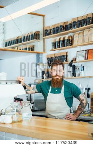 Bearded barista in white apron with tattooed hands in coffee shop