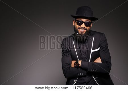 Happy afro american man in fashion cloth standing with arms folded over black background