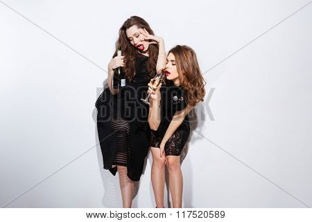 Two sexy women in night dress drinking champagne isolated on a white background