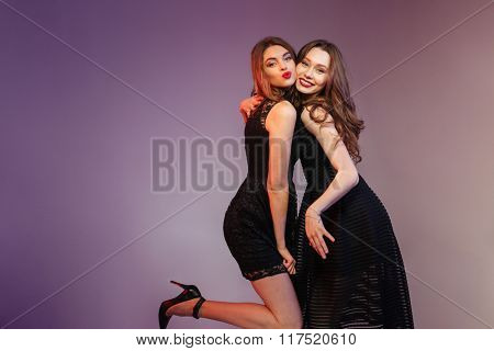 Happy two women in night black dress posing over purple background