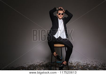 Handsome man in trendy cloth sitting on the chair over black background