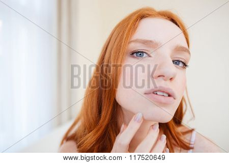 Closeup of beautiful young woman with red hair touching and considering her face