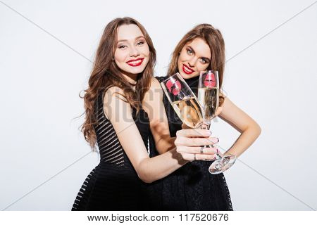 Smiling two women in night dress holding glass with champagne isolated on a white background