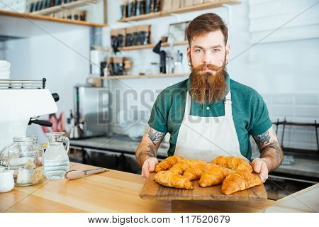 Attractive bearded barista standing in cafe and holding wooden board with croissants