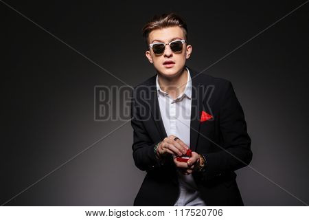 Handsome man holding box with a proposal ring over black background