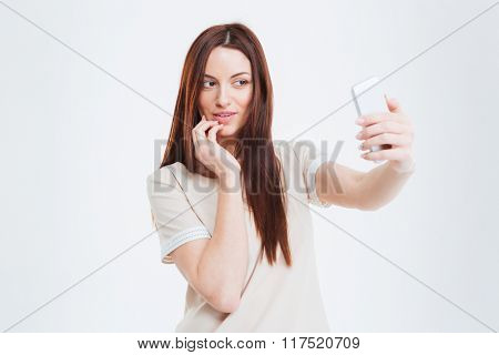 Happy woman making selfie photo on smartphone isolated on a white background