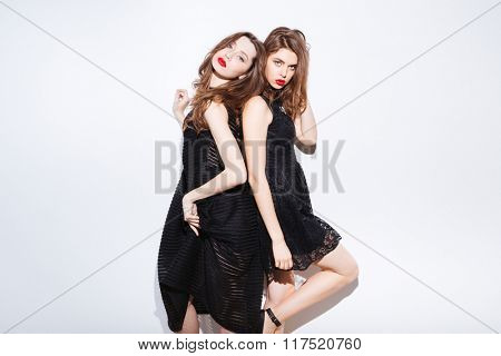 Two beautiful women in night dress posing isolated on a white background