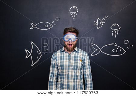 Amazed bearded man in diving mask standing with open mouth over blackboard background