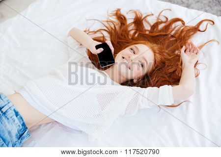 Attractive cheerful young woman with long red hair lying and holding blank screen mobile phone