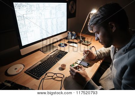 Serious handsome young man using soldering iron for fixing smartphone sitting in dark room